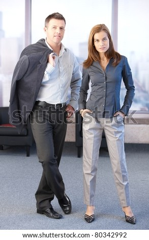 Young attractive businesspeople standing in office lobby.? - stock photo