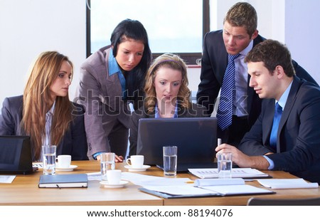 Young attractive businesswoman and her team, sitting at conference table and work on laptop computer - stock photo