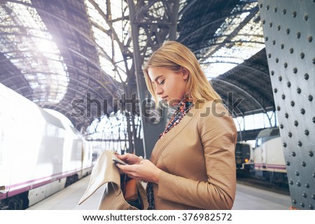young attractive businesswoman booking of train tickets online.beautiful young blond woman writes a message to a friend with information about their train - stock photo