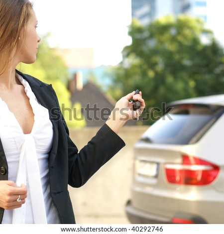 Young attractive businesswoman closes the door of her car - stock photo