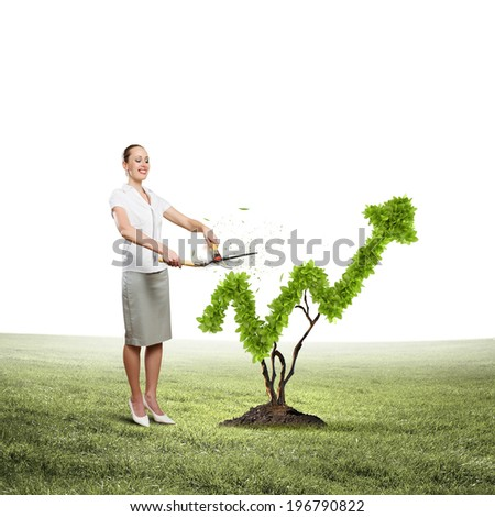 Young attractive businesswoman cutting lawn in shape of graph