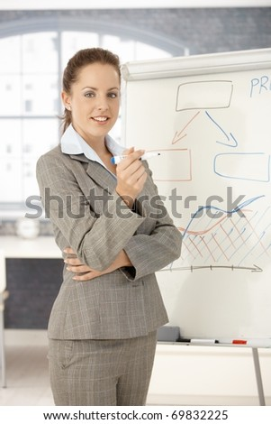 Young attractive businesswoman doing presentation in office, standing front of whiteboard, smiling.? - stock photo