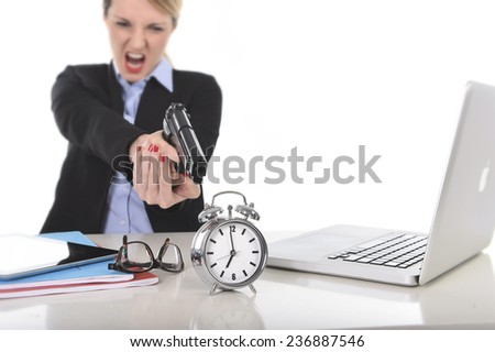 young attractive businesswoman furious and angry working with computer laptop pointing gun to alarm clock in out of time, long hours of work and project deadline stress - stock photo
