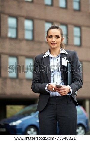 young attractive businesswoman in shirt and suit, office building as background - stock photo