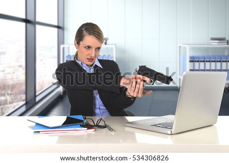 young attractive businesswoman pointing gun to computer laptop sitting at desk desperate and stressed having problems with work project working at modern business district office