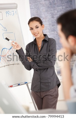 Young attractive businesswoman presenting in office over whiteboard, smiling.? - stock photo