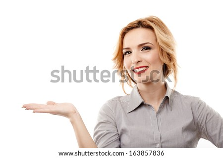 Young attractive businesswoman showing copyspace to the left and smiling, isolated on white background