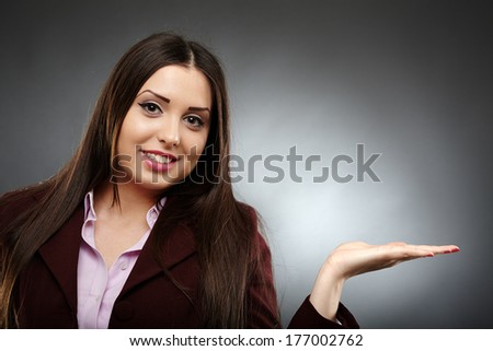 Young attractive businesswoman showing copyspace to the right and smiling over gray background - stock photo