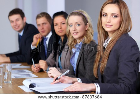 Young attractive businesswoman sitting at conference table with 4 more people, working on some paperwork - stock photo