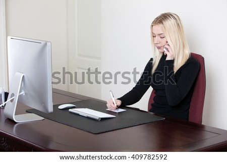 young attractive businesswoman sitting at ther workplace, talking on the phone and writes on paper - stock photo