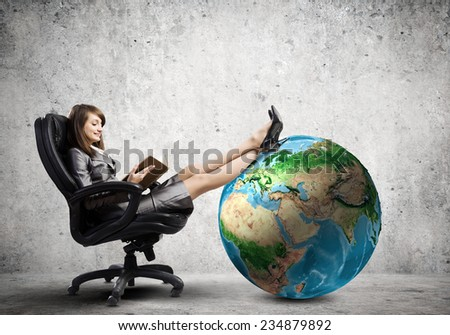 Young attractive businesswoman sitting in chair and reading book. Elements of this image are furnished by NASA - stock photo