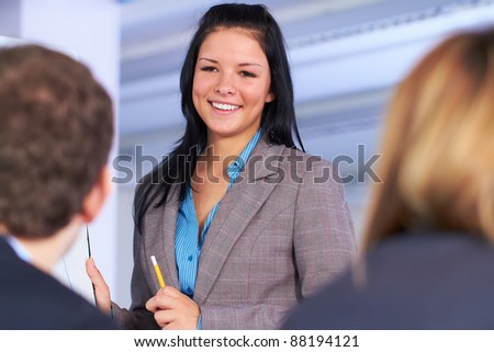 Young attractive businesswoman standing next to flip chart, very positive face expression, simply happy. - stock photo