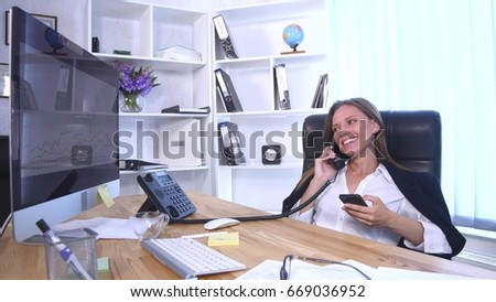 Young attractive businesswoman talking on telephone and using smartphone in the office and smiling.