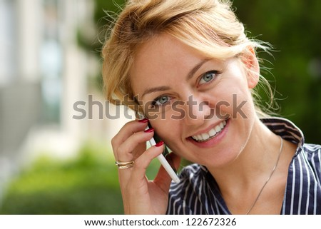 Young attractive businesswoman talking on the phone smiling - stock photo