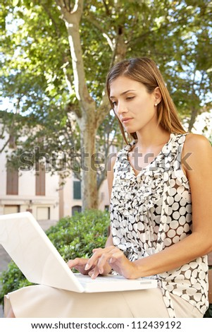 Young attractive businesswoman using a pc laptop computer while sitting on a wooden bench in a city park. - stock photo