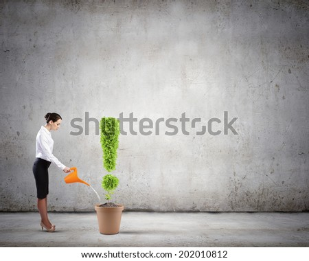 Young attractive businesswoman watering plant in pot with can - stock photo