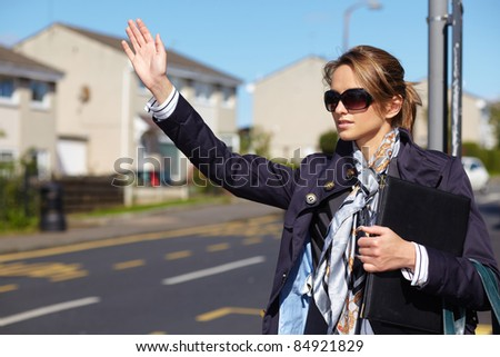 Young attractive busy businesswoman calling taxi, outdoor shoot with blurred buildings and street as background