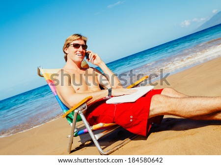 Young Attractive Casual Businessman Entrepreneur Relaxing at the Beach with Laptop Computer Talking on Cell Phone - stock photo
