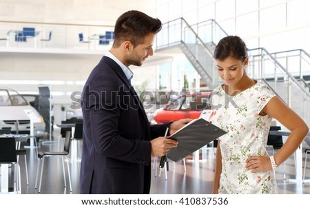 Young attractive casual caucasian woman at car dealership reviewing business papers. Male saloon sales manager wearing suit, clipboard in hand. Communication, looking down, smiling, hand on hip. - stock photo