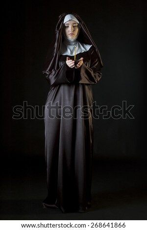 Young attractive catholic nun holding candle. Photo on black background.