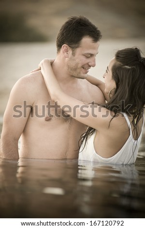 Young attractive caucasian couple flirting on beach in water