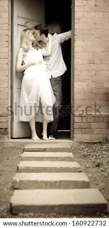 Young attractive caucasian couple leaning against door frame kissing - stock photo