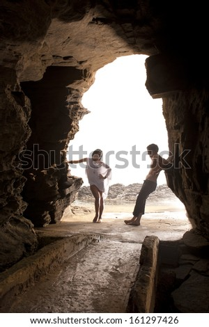 Young attractive caucasian couple leaning on rock archway - stock photo