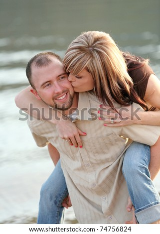 young attractive Caucasian couple playing together on beach - stock photo