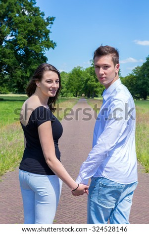 Young attractive caucasian man and woman walking hand in hand looking back - stock photo