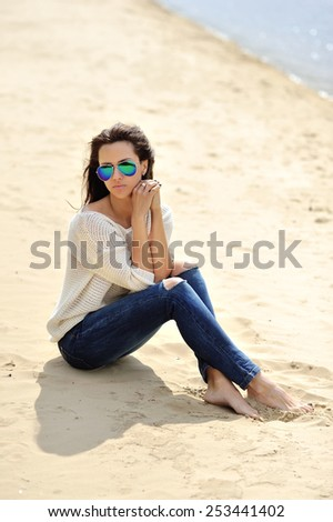 Young attractive cheerful woman sitting on a sand - stock photo