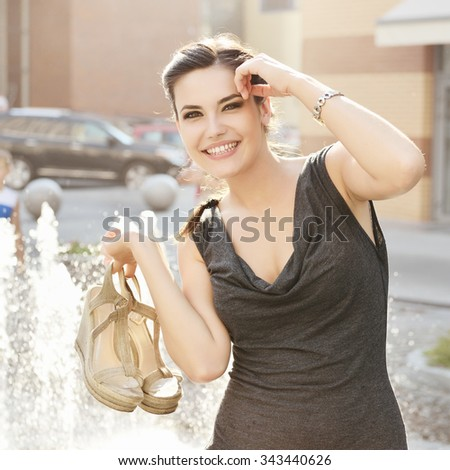 Young attractive cheerful woman walking in city, summer hot outdoor near fountain. - stock photo