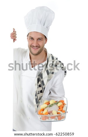 Young attractive chef caucasian male with hat and white uniform showing a raw tenderloin piece and fresh vegetables and herbs in glassware. Studio shot. White background. - stock photo