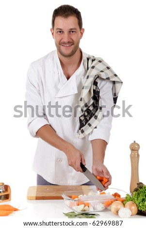 Young attractive chef caucasian male with uniform preparing a tenderloin piece with fresh vegetables and herbs. Studio shot. White background. - stock photo