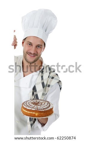 Young attractive chef male with hat and white uniform showing a cake. Studio shot. White background. - stock photo