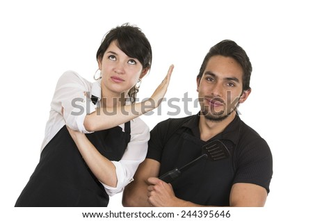 young attractive couple chefs wearing black apron arguing isolated on white - stock photo