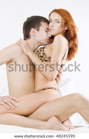Young attractive couple embracing in bedroom - stock photo