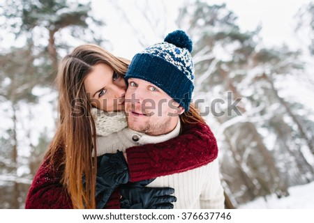 young attractive couple enjoying walk together in winter forest, happy lifestyle concept - stock photo