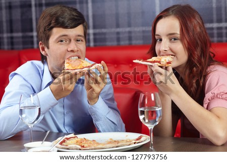 Young attractive couple having fun in restaurant eating pizza together - stock photo