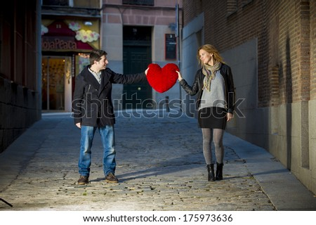 young attractive couple holding a big red heart looking at each other.  - stock photo