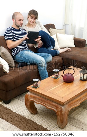 young attractive couple in a sofa watching news tablet - stock photo