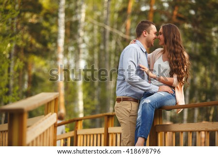 Young attractive couple in love at a park. Young couple hugging in their new country wooden house. Elegentno dressed businessmen. Family values, adult life. We bought a new house, new housing - stock photo