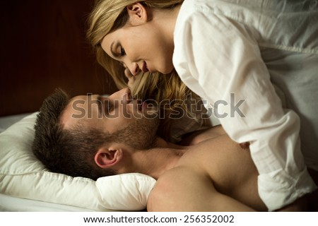 Young attractive couple in love hugging in bed - stock photo