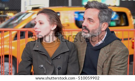 Young attractive couple looking off into the distance sitting on New York City park bench. Yellow taxi cab drive by in background. Urban hipster date night.