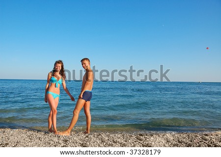 young attractive couple on summer beach against blue sea