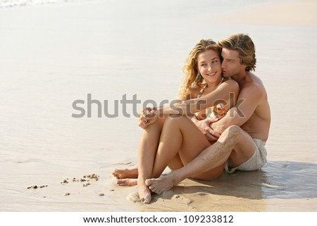 Young attractive couple sitting together by the shore on a golden sand beach while on vacation. - stock photo