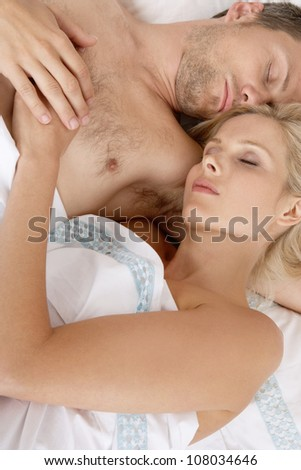 Young attractive couple sleeping together in bed.