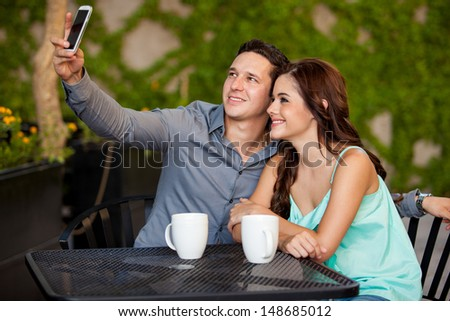 Young attractive couple taking a photo with a cell phone during their first date at a cafe - stock photo