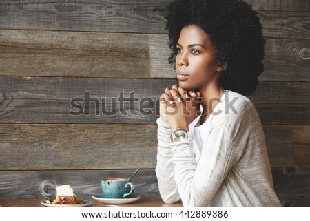 Young attractive dark skinned female at a cafe table, drinking coffee with cake, sitting in thinking pose, resting chin on her clasped hands, looking away with a reflective expression on her face - stock photo