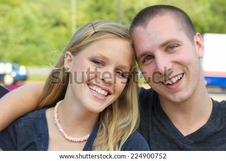 Young Attractive Dating Couple Happy in Love Blonde Boyfriend with Arm Around Girlfriend Smiling Friendly  - stock photo