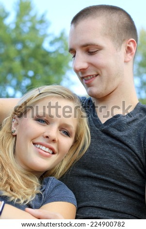 Young Attractive Dating Couple Happy in Love Blonde Boyfriend with Arm Around Girlfriend Smiling Friendly Smiling and Cuddling - stock photo